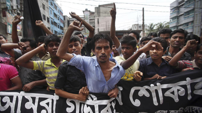 """Workers at a garment factory just streets away from the recently collapsed garment factory building, protest as they refuse to work when they found cracks in their current office building, Tuesday, April 30, 2013 in Savar, near Dhaka, Bangladesh.   A top Bangladesh court on Tuesday ordered the government to """"immediately"""" confiscate the property of a collapsed building's owner, as thousands of protesters demanding death penalty for the man clashed with police, leaving 100 people injured. (AP Photo/Wong Maye-E)"""