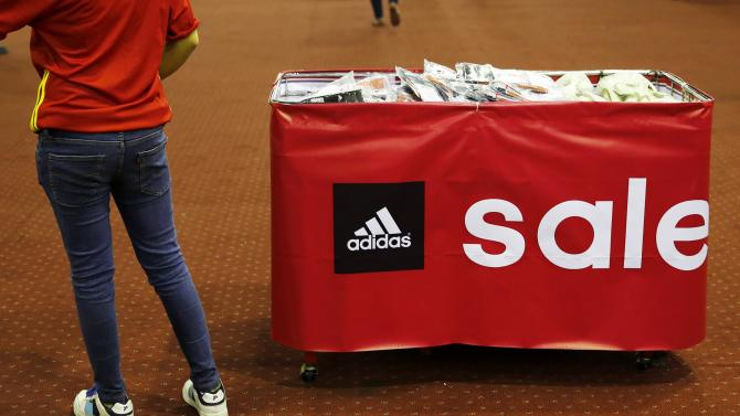 A promoter stands near goods during an Adidas clearance sale in Jakarta