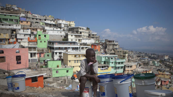 """In this March 21, 2013 photo, Nicolas Richnado watches over buckets filled with water as he waits for his mother to return from carrying a bucket of water to their home in Jalousie, a cinder block shantytown recently painted in colors in Petionville, Haiti. A $1.4 million effort titled """"Beauty versus Poverty: Jalousie in Colors"""" is part of a government project to relocate people from the displacement camps that sprouted up after Haiti's 2010 earthquake.  (AP Photo/Dieu Nalio Chery)"""