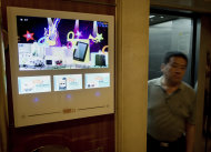 <p>               A Chinese man walks past a TV advertising screen by Focus Media Holding Ltd. on display near an apartment lift in Beijing Tuesday, Aug. 14, 2012. Just a few years after Chinese companies lined up to sell shares on Wall Street, a growing number are reversing course and pulling out of U.S. exchanges. This week, Focus Media Holding Ltd., announced its chairman and private equity firms want to buy back its U.S.-traded shares and take the Shanghai-based advertising company private. The deal would value Focus Media at $3.5 billion, according to financial information firm Dealogic. (AP Photo/Andy Wong)