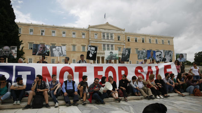 Protesters holding placards with the images of contemporary Greek poets and artists, take part in a protest in front of the Parliament in Athens, Friday, June 14, 2013. Workers at the Hellenic Broadcasting Corp. or ERT have continued to occupy the broadcaster's headquarters and maintain online and satellite broadcasts since the government shut down the station Tuesday, citing the need to make austerity cuts and promising to relaunch with fewer staff before the end of the summer. (AP Photo/Kostas Tsironis)