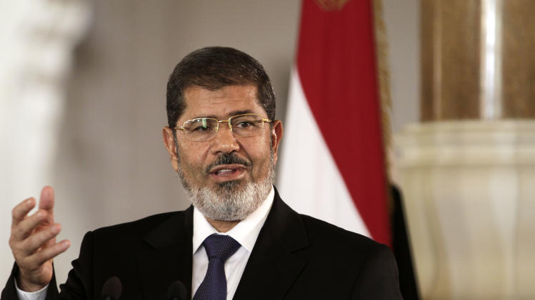 FILE - In this Friday, July 13, 2012 file photo, Egyptian President Mohammed Morsi holds a joint news conference with Tunisian President Moncef Marzouki, unseen, at the Presidential palace in Cairo, Egypt. The Egyptian army sealed off the presidential palace with barbed wire and armored vehicles Thursday as protesters defied a deadline to vacate the area, pressing forward with demands that Islamist leader Mohammed Morsi rescind decrees giving himself near-absolute power and withdraw a disputed draft constitution.(AP Photo/Maya Alleruzzo, File)