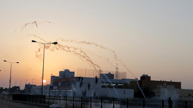 Tear gas fired by riot police lands in front of protesters during clashes after a protest in the village of Sitra south of Manama