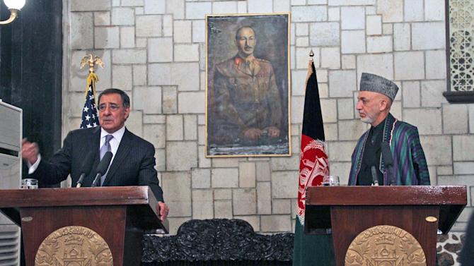US Defence Secretary Leon Panetta,  left,  talks with journalists during a joint press conference with Afghan President Hamid Karzai, in Kabul, Afghanistan, Thursday, Dec. 13, 2012. A suicide bomber killed four people on Dec. 13 outside a US airbase in southern Afghanistan, hours after Defence Secretary Leon Panetta visited, said officials. An official with the NATO-led military force said Panetta had left Kandahar airbase hours before the bombing. (AP Photo /SSabawoon, Pool)