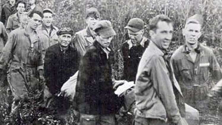 In this 1944 photo provided by the University of Vermont Special Collections, rescuers reach the base of Camels Hump carrying James Wilson, a 19-year-old Army airman who survived a plane crash on the mountain in Vermont. Peter Mason, of Pasadena, Calif., and Rolland Lafayette, of Waterbury, Vt., the only surviving rescuers, were honored for their role in the rescue Friday, June 20, 2014 at the State House in Montpelier, Vt. (AP Photo/University of Vermont Special Collections)