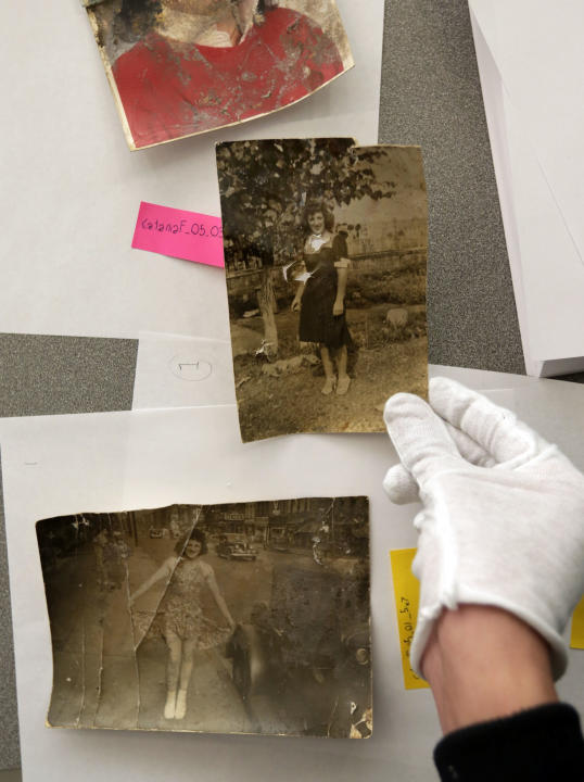 In this Saturday, Feb. 2, 2013 photo, damaged photos belonging to Florence Catania, of Deer Park, N.Y., are evaluated during restoration by Operation Photo Rescue-Hurricane Sandy, at New York's School