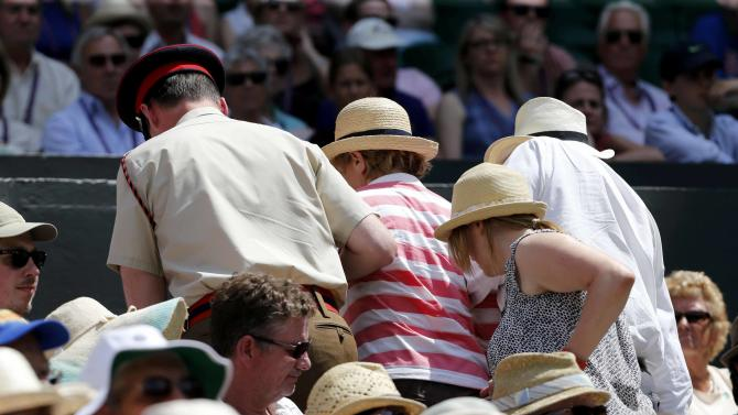A spectator is helped off Centre Court at the Wimbledon Tennis Championships in London