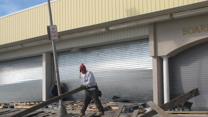 In a Nov. 1, 2012 photo, a worker sorts through shattered boards on the Point Pleasant Beach N.J. boardwalk, three days after Superstorm Sandy pounded the resort.  Point Pleasant Beach has reached an agreement with the owners of Jenkinson's Boardwalk to drop a proposed midnight bar closing law in return for the company dropping lawsuits against the town. Jenkinson's also will contribute up to $1 million to help rebuild the storm-damaged boardwalk. (AP Photo/Wayne Parry)