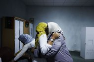 Libyan election workers embrace each other after the ringing of a bell marking the end of voting at a polling station in Tripoli during Libya's General National Assembly election on July 7. Liberals appeared to have the edge on Islamists as a key figure in the revolt that ousted Moamer Kadhafi urged national unity on Monday with Libya still days away from the final results