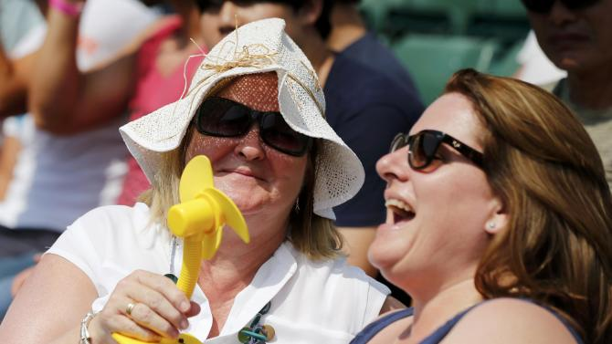Spectators use mini electric fans to stay cool at the Wimbledon Tennis Championships in London