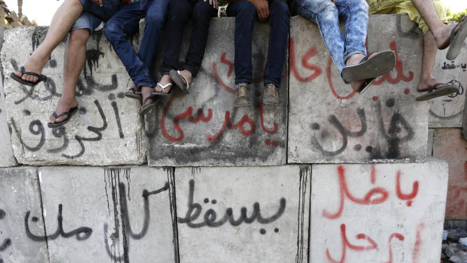 """Opponents of Egypt's Islamist President Mohammed Morsi set on cement blocks with Arabic that reads: """"Void, Morsi traitor, Down"""" as protest outside the presidential palace in Cairo, Egypt, Monday, July 1, 2013. Hundreds of thousands thronged the streets of Cairo and cities around the country Sunday and marched on the presidential palace, filling a broad avenue for blocks, in an attempt to force out the Islamist president with the most massive protests Egypt has seen in 2½ years of turmoil. (AP Photo/Hassan Ammar)"""