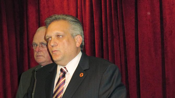 Nassau County Executive Edward Mangano discusses the shooting death of Police Officer Arthur Lopez, in picture at right, Tuesday, Oct. 23, 2012, as Police Commissioner Thomas Dale stands behind at police headquarters in Mineola, N.Y.  A motorist fleeing a possible hit-and-run traffic accident fatally shot Lopez in broad daylight Tuesday near the Belmont racetrack and then apparently killed another driver not far away during a carjacking, authorities said. (AP Photo/Frank Eltman)