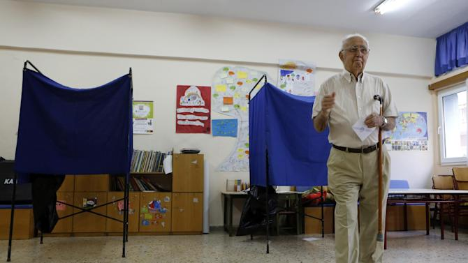 An elderly man casts his vote at a polling station in Athens, Sunday, July 5, 2015. Greeks began voting early Sunday in a closely-watched, closely-contested referendum, which the government pits as a choice over whether to defy the country's creditors and push for better repayment terms or essentially accept their terms, but which the opposition and many of the creditors paint as a choice between staying in the euro or leaving it. (AP Photo/Petros Karadjias)