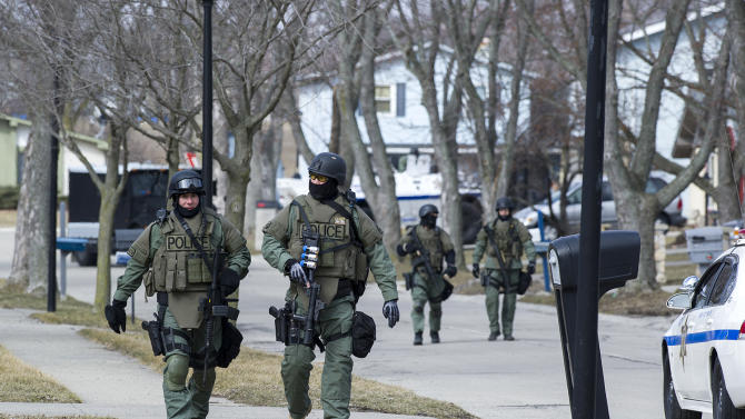 EST officers return after searching a home which was the last known address of Kenneth Knight Wednesday, March 20, 2013 in Fort Wayne, Ind. Knight pulled a woman off a city bus, fatally shot her and then took a 3-year-old boy hostage before a sniper killed him during a police standoff. (AP Photo/The Journal-Gazette, Swikar Patel)  NEWS-SENTINEL OUT; MANDATORY CREDIT; NO SALES; MAGS OUT