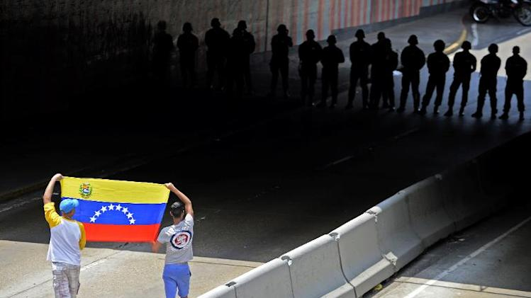 Demonstrators show a Venezuelan national flag to riot police during a protest against the government of Venezuelan President Nicolas Maduro in Caracas on March 8, 2014