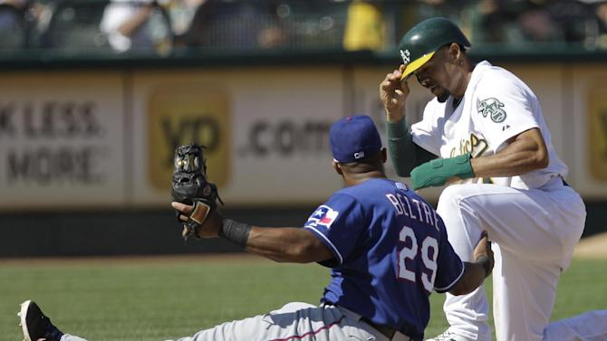 Oakland Athletics' Coco Crisp, right, adjusts his helmet after stealing third base against Texas Rangers third baseman Adrian Beltre (29) in the eighth inning of a baseball game on Thursday, Sept. 22, 2011, in Oakland, Calif. (AP Photo/Ben Margot)