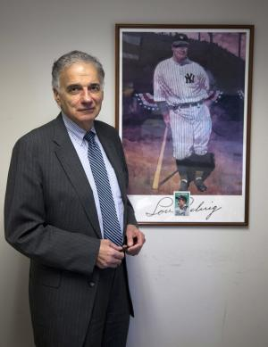 "In this Tuesday, Dec. 13, 2011 photo, Ralph Nader stands next to his poster of Lou Gehrig in his office in Washington. Over a five-decade career in America's consumer movement, Nader has fought against the auto industry over safety and has targeted businesses he blamed for water pollution, nursing home fraud, and more. Now the sports industry is drawing an increasing share of Nader's attention and anger - it's ""spinning out of control,"" he says, amid sex-abuse scandals, labor strife and rampant commercialization. (AP Photo/Evan Vucci)"