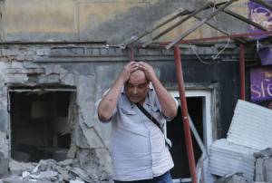Man reacts as he stands in front of a building damaged by, what locals say, was recent shelling by Ukrainian forces, in Donetsk