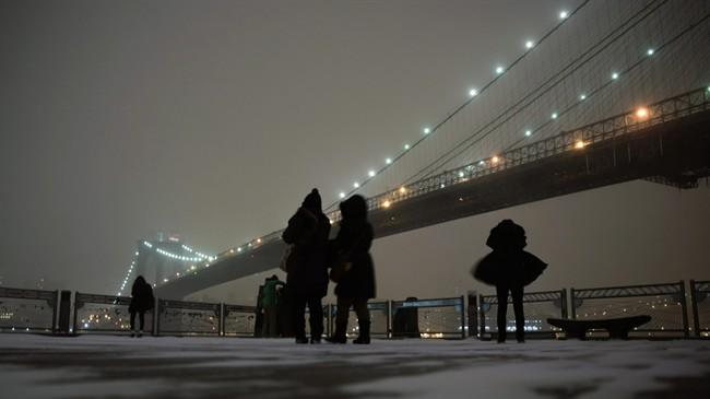 FILE - This Jan. 2, 2014 file photo shows visitors on the waterfront in Brooklyn to photograph the Brooklyn Bridge during a winter storm in New York. If you don't mind the cold, walking across the Brooklyn Bridge is a classic New York City outing for tourists, one of a number of things Super Bowl visitors might consider doing when they're in town for the big game. (AP Photo/Peter Morgan, File)