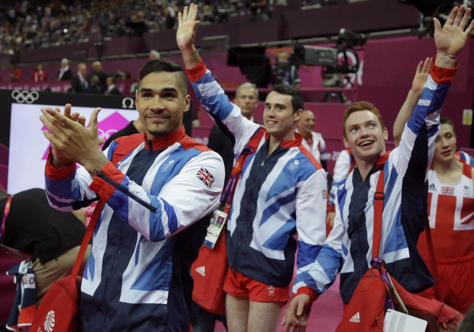 Great Britain's gymnasts Louis Smith , left, Kristian Thomas and Daniel Purvis acknowledge the crowd after winning the bronze at the Artistic Gymnastic men's team final at the 2012 Summer Olympics, Monday, July 30, 2012, in London. (AP Photo/Julie Jacobson)