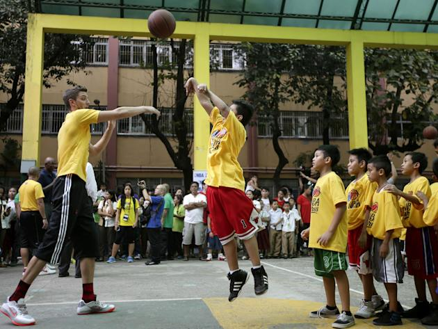 Houston Rockets' Chandler Parsons attempts to block a jump shot by an elementary student during a basketball clinic at Aurora Quezon Elementary School Wednesday, Oct. 9, 2013, in Manila, Philippines.