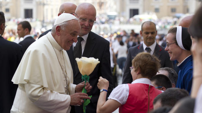 Pope Francis is presented with a paper flower by a sick girl as he leaves St. Peter's square at the Vatican after his weekly general audience Wednesday, June 26, 2013. (AP Photo/Alessandra Tarantino)