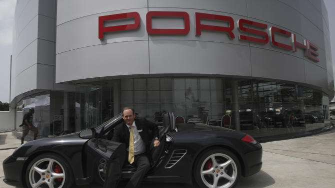 Michael Wagner, the Porsche SA brand manager for Stallion Motors Ltd. of Nigeria, sits in a new Porsche Carrera 911 outside of a showroom for the luxury brand on Victoria Island in Lagos, Nigeria, Friday March 16, 2012. The wealthy elite in Nigeria _ upstart business owners, oil industry executives and corrupt politicians _ have a healthy appetite for top shelf brands, but have had to shop in Dubai, London and Paris to find such brands. Now though, sellers of luxury goods are opening stores in Nigeria where seemingly gratuitous displays of wealth are the norm.(AP Photos/Sunday Alamba)