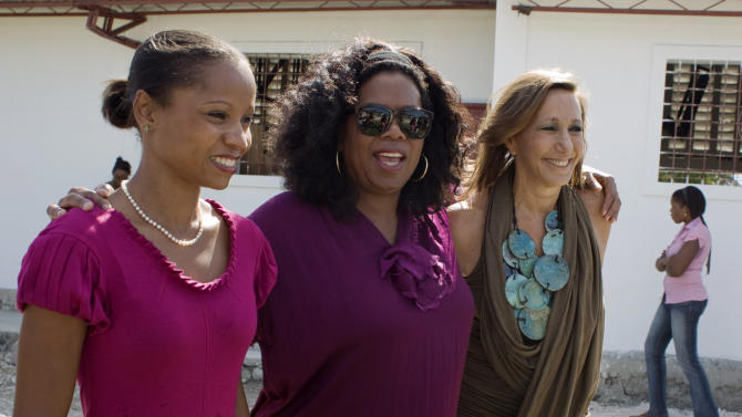 Oprah Winfrey, center, poses for a picture with the owner of the store and workshop Caribbean Craft, Magalie Dresse, left, and U.S. fashion designer Donna Karan during a visit to Caribbean Craft in Port-au-Prince, Haiti, Tuesday Dec. 13, 2011. (AP Photo/Dieu Nalio Chery)