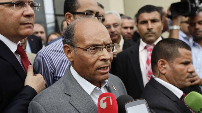 Tunisian President Marzouki speaks to members of the media after submitting his candidacy for the upcoming presidential elections, in Tunis
