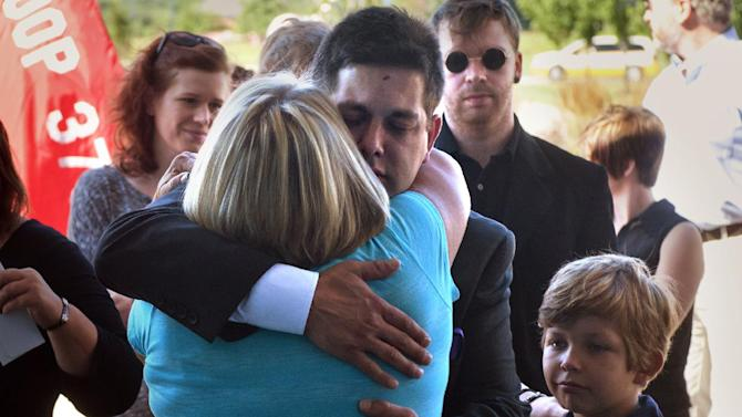 Conner Verkerke's dad Jared Verkerke gets a hug as families and friends arrive for the memorial service for Connor Verkerke at Cornerstone Church in Caledonia, Mich., Wednesday, Aug. 13, 2014. At right is little brother Kameron Verkerke. Connor, 9, was stabbed by a 12-year-old on a playground. (AP Photo/The Grand Rapids Press, Chris Clark)