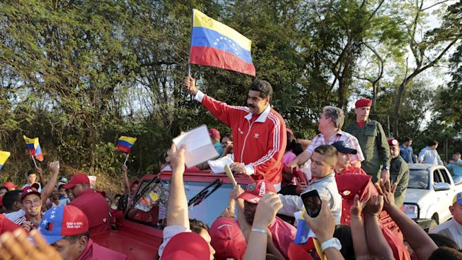Venezuela's President Nicolas Maduro waves a Venezuelan national flag during a campaign rally at Valles del Tuy in Miranda state