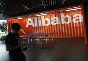 An employee walks past a logo of Alibaba (China) Technology Co. Ltd during a media tour organised by government officials at its headquarters on the outskirts of Hangzhou