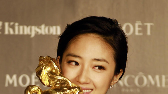"""Taiwanese actress Gwei Lun-Mei kisses her award for the Best Actress for the film """"GF * BF"""" at the 49th Golden Horse Awards at the Luodong Cultural Working House in Yilan County, Taiwan, Saturday, Nov. 24, 2012. The Golden Horse awards are the Chinese-language film industry's biggest annual events. (AP Photo/Wally Santana)"""