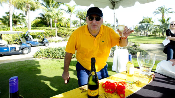 Chef Jose Andres poses for photos in his food station on the Miami Beach, Fla. golf course, Saturday, Feb. 23, 2013. Nearly a dozen A-list chefs took to the links early Saturday during the South Beach Wine and Food Festival for a battle of the chefs during a golf tournament hosted by Andres.   (AP Photo/J Pat Carter)