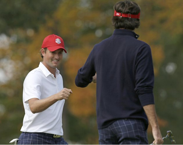 USA's Webb Simpson, left, is congratulated by Bubba Watson after Simpson made a putt to win the first hole during a four-ball match at the Ryder Cup PGA golf tournament Friday, Sept. 28, 2012, at