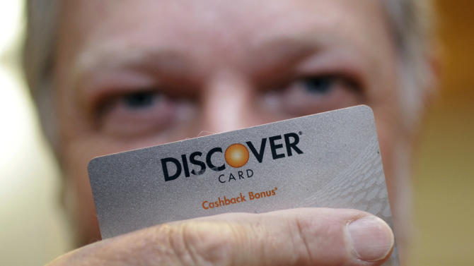 Steve Wheelock holds up his Discover Card in San Francisco, Wednesday, June 22, 2011. Discover Financial Services said Thursday, June 23, its second-quarter profit more than tripled as customers used their cards more and got better about making payments on time.(AP Photo/Paul Sakuma)