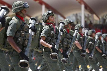Venezuelan soldiers march during a military parade to commemorate the first anniversary of the death of Venezuela's late president Hugo Chavez in Caracas
