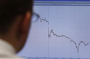 A trader poses in front of a screen on a trading floor in London