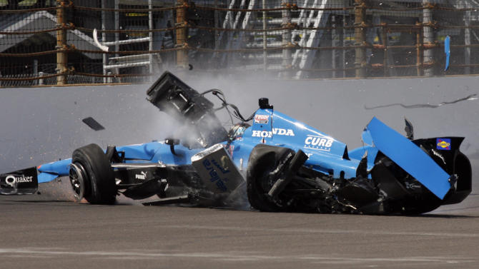 IndyCar driver Bryan Clauson slides through the first turn after crashing into the wall during his qualification run on the first day of qualifications for the Indianapolis 500 auto race at the Indianapolis Motor Speedway in Indianapolis, Saturday, May 19, 2012. (AP Photo/Tom Hemmer)