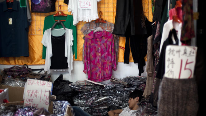 A vendor sleeps at a silk clothing store while waiting for customers at a summer consumer fair in Beijing, China, Wednesday, Aug. 15, 2012. Facing a collapse in export growth and weak consumer spending, Beijing is avoiding an aggressive stimulus and sticking to a gradual strategy of small interest rate cuts and modest spending.(AP Photo/Alexander F. Yuan)