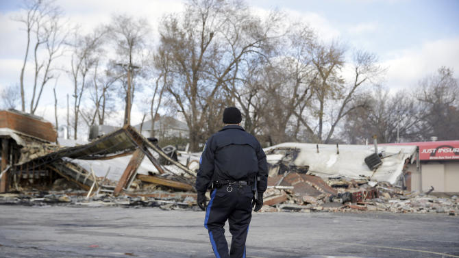 A member of the Missouri Highway Patrol walks past a building burned to the ground, Tuesday, Nov. 25, 2014, in Dellwood, Mo. The building and several others in-and-around Ferguson were burned during protests after a grand jury decided not to indict a Ferguson police officer in the shooting death of Michael Brown. (AP Photo/Jeff Roberson)