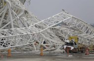 A collapsed metal structure sits on the ground at Itaquerao Stadium in Sao Paulo, Brazil, Wednesday, Nov. 27, 2013. The accident that resulted in the death of at least two workers, occurred when a construction crane crashed into a 500-ton metal structure that in turn cut through the outer walls of the venue, destroying rows of seats and slamming into a massive LED panel that runs across the stadium's facade. The stadium is slated to host the 2014 World Cup opener. (AP Photo/Nelson Antoine)