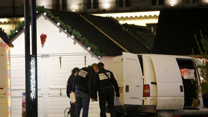 French police investigators work near a van which was driven into a crowd, injuring ten people, including five seriously wounded, according to French media, in Nantes