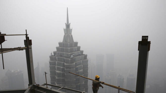 In this Jan. 16, 2013 photo, a worker carries steel bars on top of the construction site of Shanghai Tower while the skyscrapers in the Pudong area are shrouded in the heavy fog in Shanghai, China.   China's economy rebounded in the final quarter of 2012 but optimism was tempered by warnings the shaky recovery could be vulnerable to a possible downturn in global trade. Economic growth rose to 7.9 percent in the three months ending in December as a recovery from China's deepest slowdown since the 2008 global crisis took hold, data showed Friday. (AP Photo)  CHINA OUT