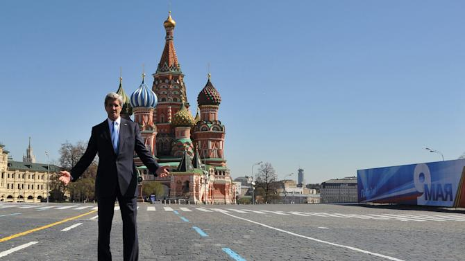 U.S. Secretary of State John Kerry gestures in front of St. Basil Cathedral while walking in Red Square, with a poster marking the upcoming Victory Day at right,  in Moscow, Tuesday, May 7, 2013. John Kerry is making his case to Russian President Vladimir Putin for Russia to take a tougher stance on Syria at a time when Israel's weekend air strikes against the beleaguered Mideast nation have added an unpredictable factor to the talks. (AP Photo/Mladen Antonov, Pool)
