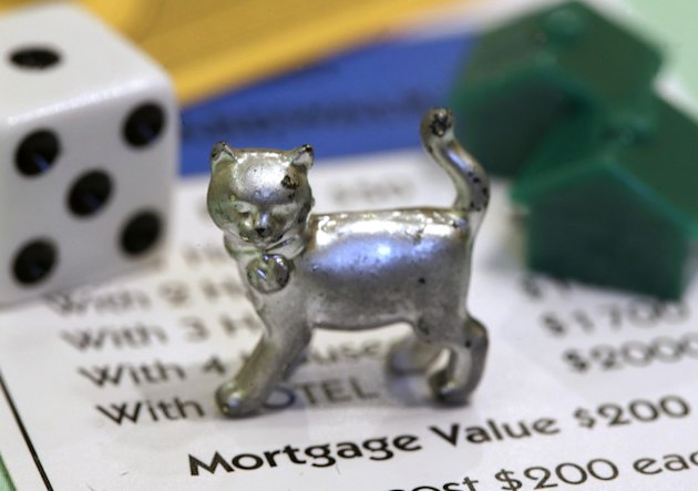 The newest Monopoly token, a cat, rests on a Boardwalk deed next to a die and houses at Hasbro Inc. headquarters, in Pawtucket, R.I., Tuesday, Feb. 5, 2013. Voting on Facebook determined that the cat