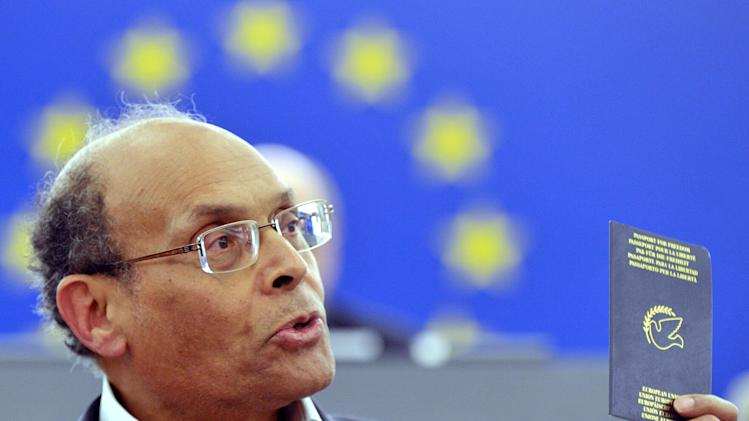 "Moncef Marzouki, President of Tunisia, shows his ""Liberty passport"" he was given as he was living in exile in France years ago and was forbidden to return his native country, during a statement at the European Parliament in Strasbourg, eastern France, Wednesday, Feb.6, 2013. Marzouki, who is from a secular party in the governing coalition, was in Strasbourg addressing the European Parliament and said the assassination was a threat against all of Tunisia. Chokri Belaid, a Tunisian opposition leader critical of the Islamist-led government and violence by radical Muslims was shot to death Wednesday _ the first political assassination in post-revolutionary Tunisia. (AP Photo/Christian Lutz)"