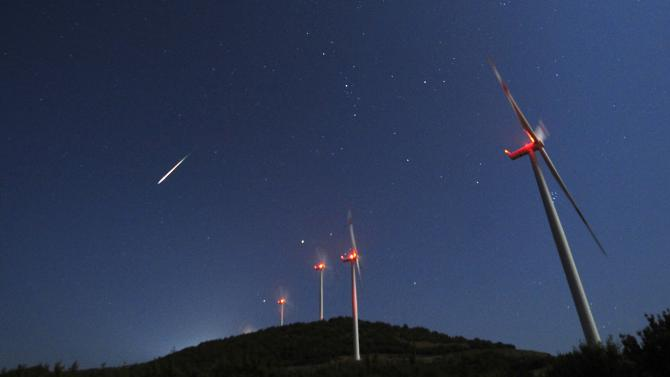 A meteor streaks across the sky during the Perseid meteor shower at a windmill farm near Bogdanci