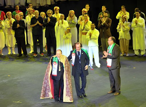 Algerian President Abdelaziz Bouteflika, standing at left, and Lebanese choreographer Abdelhalim Caracalla, center, appear after a show marking 50 years of Algeria's Independence in Algiers, early Thursday, July 5, 2012. As the Muslim North African nation celebrates 50 years of nationhood on Thursday, Algeria and France are locked in a  war of memories that still weighs on lives on both sides of the Mediterranean, and on the two countries' ties. (AP Photo/Anis Belghoul)