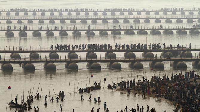Hindu devotees take a dip at Sangam, the confluence of the Rivers Ganges, Yamuna and mythical Saraswati as others cross a make shift bridge, on one of the most auspicious day Makar Sankranti,  the first day of the Maha Kumbh Mela, in Allahabad, India, Monday, Jan. 14, 2013. Millions of Hindu pilgrims are expected to take part in the large religious congregation of a period of over a month on the banks of Sangam during the Maha Kumbh Mela in January 2013, which falls every 12th year, where devotees wash themselves in the waters of the Ganges believing that it washes away their sins and ends the process of reincarnation. (AP Photo /Rajesh Kumar Singh)